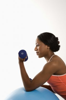 Profile woman lifting dumbbell.