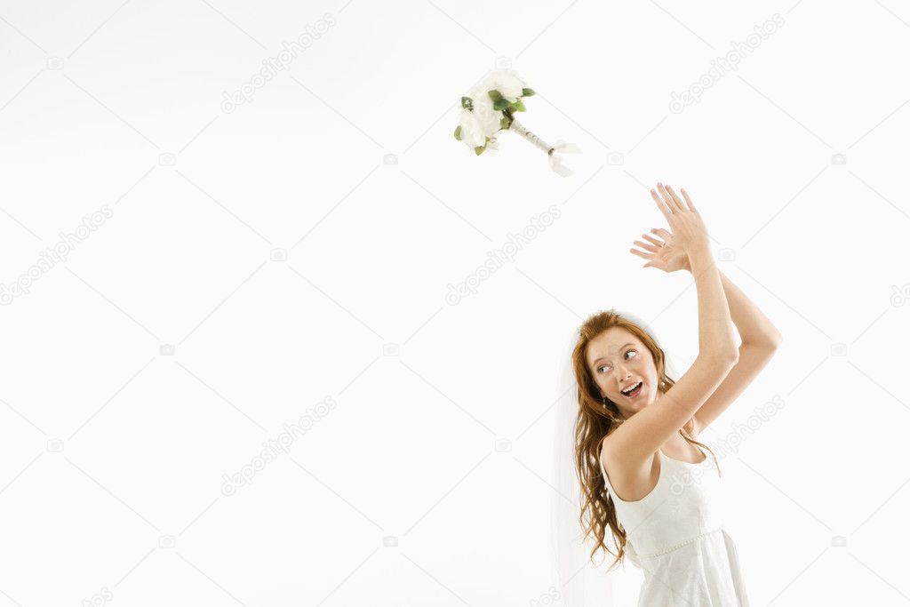 Portrait of Caucasian bride tossing bouquet behind her.