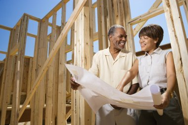 Couple Holding Building Plans on Construction Site