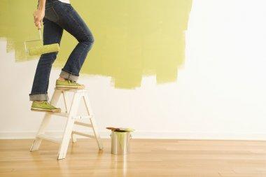 Woman painter on ladder.