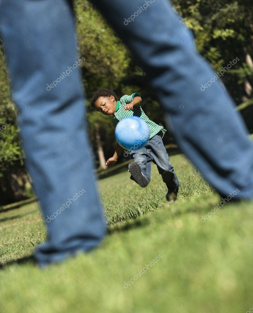 Son kicking ball to dad.