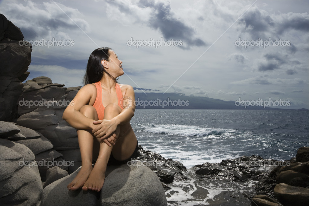 Woman sitting by ocean