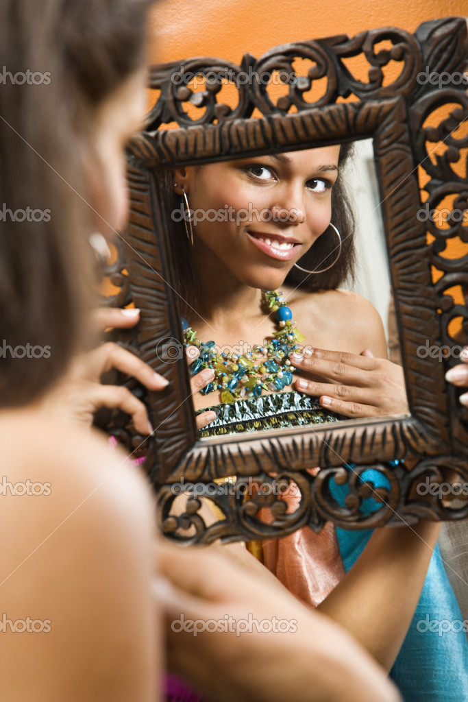 African American mid adult woman smiling at reflection in mirror wearing necklace.