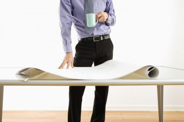 Businessman standing over plans.