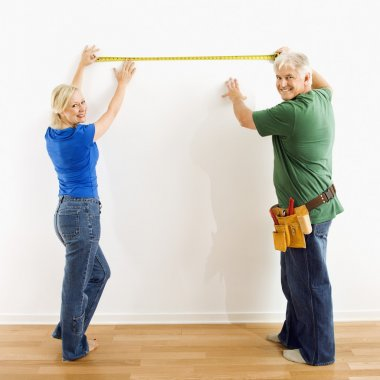 Man and woman measuring wall.