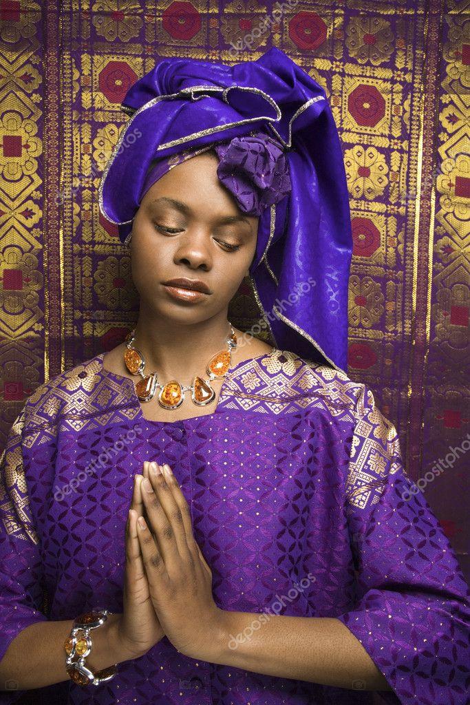 joven mujer afroamericana orando y vestido tradicional africana ...