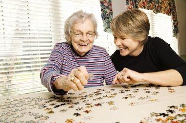 Elderly woman and a younger woman work on a jigsaw puzzle. Horizontal shot. stock vector