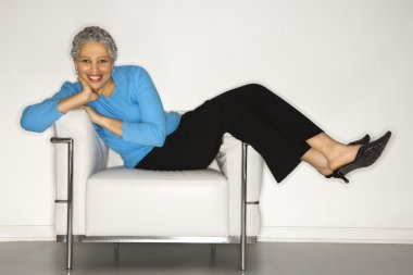Woman lying back on chair.