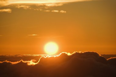 Sun rising over clouds.