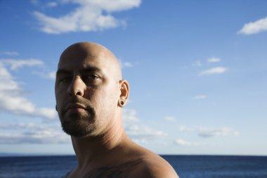 Adult bald male on beach.