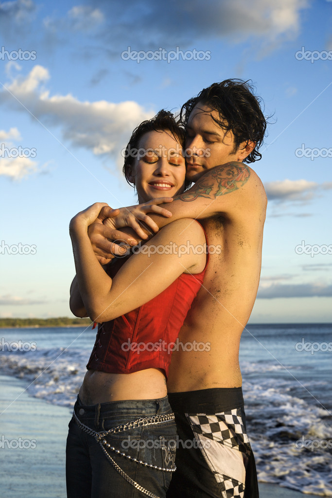 Couple embracing on beach.