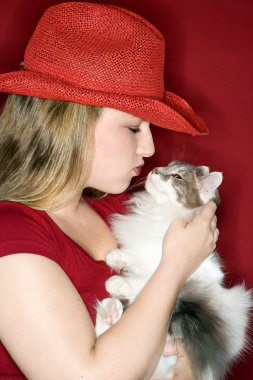 Young woman holding fluffy cat.