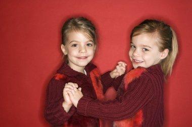 Girl child twin sisters dancing.