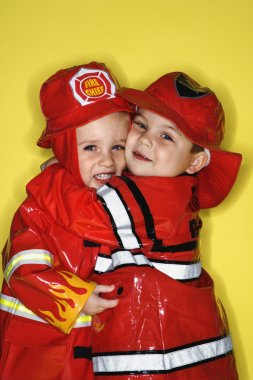Twin boys dressed as firemen.