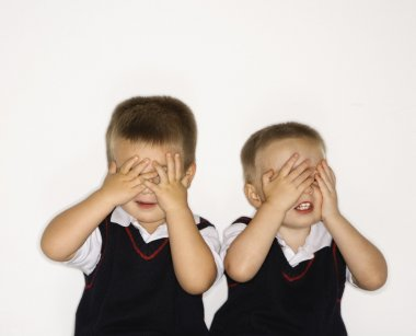 Male twins with hands over eyes.