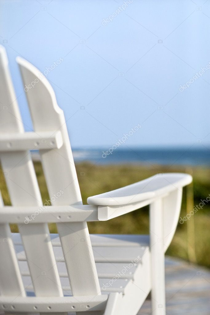 Adirondack chairs pointing toward ocean.