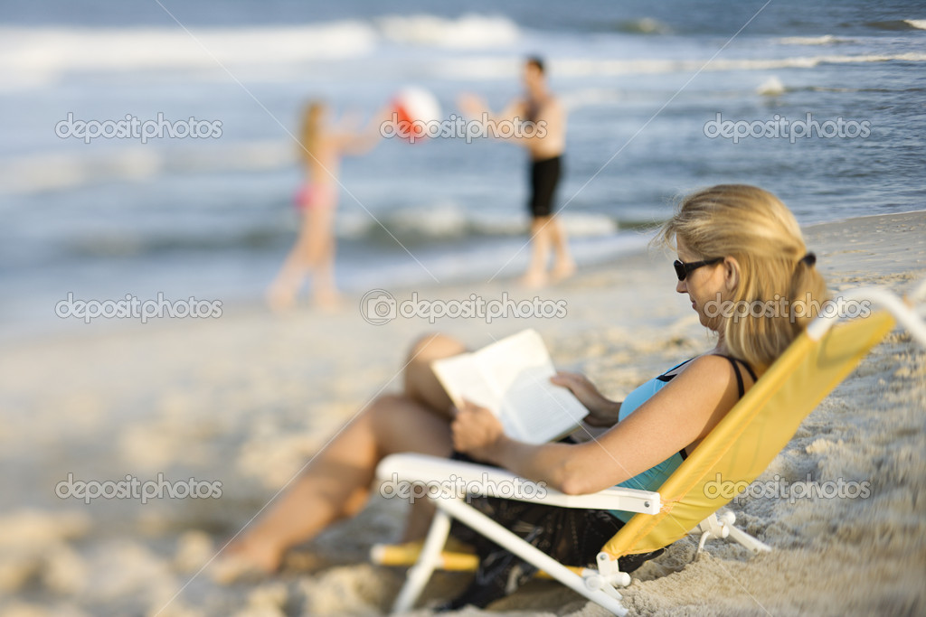 Mom reading book on beach.