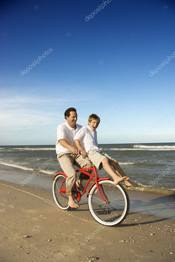 Dad riding red bicycle with son on handlebars.