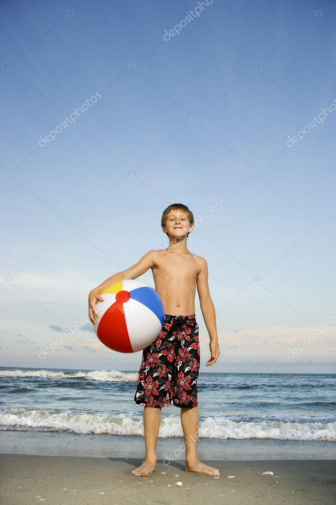 Boy holding beachball on beach.