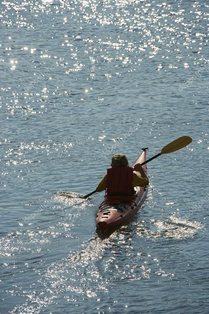 Boy paddling kayak.