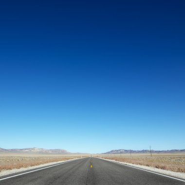Strip of highway stretching towards horizon under clear blue sky. stock vector