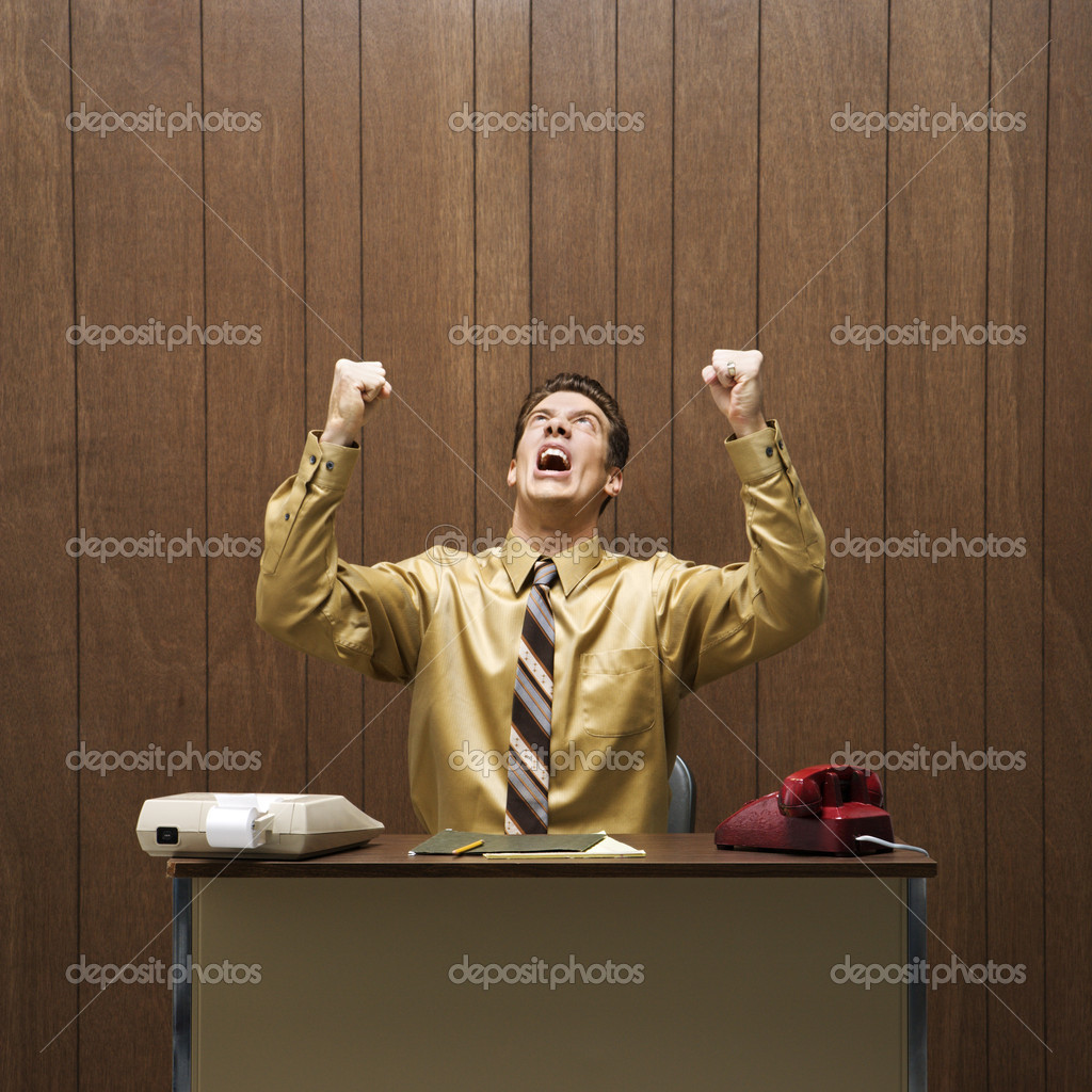 Caucasion mid-adult retro businessman sitting at desk raising fists in anger.