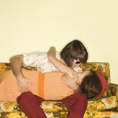 Couple kissing on sofa.
