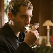 Mann trinkt Martini.