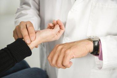 Doctor taking patient's pulse.