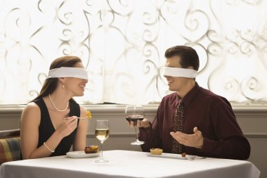 Mid adult Caucasian couple dining in a restaurant with blindfolds over eyes. stock vector