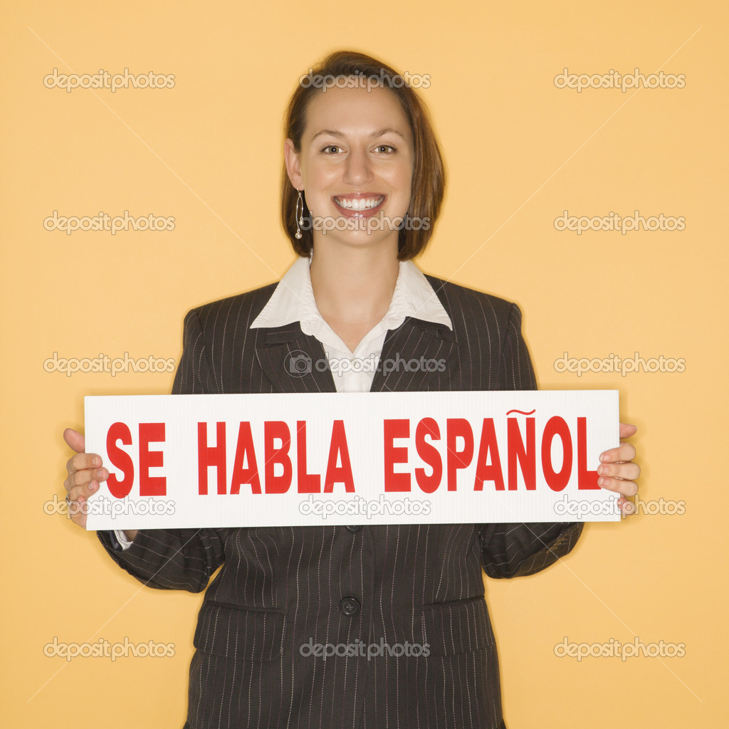 "Caucasian businesswoman smiling holding sign reading ""se habla espanol."""