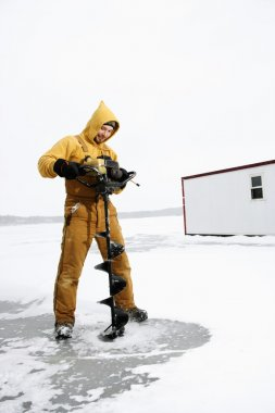 Man Drilling Hole in Ice