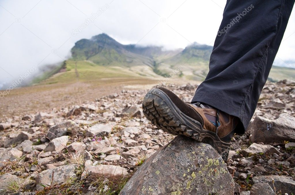 Tourist in hiking shoes standing atop the mountain