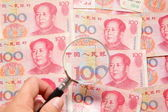 Photo Chinese money (currency) and magnifying glass