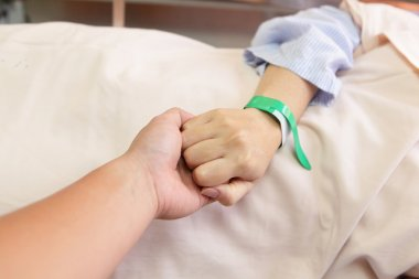 Husband grip his wife's hand before surgery