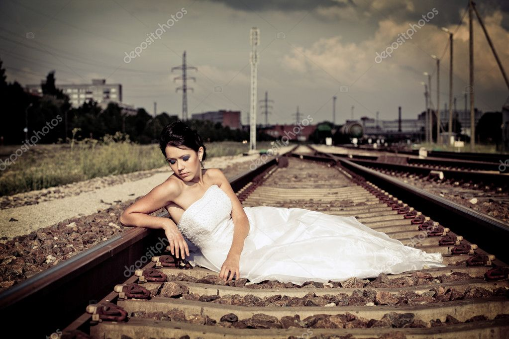 Beautiful thoughtful brunette bride is sitting on the railway and waiting