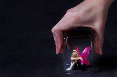 A fairy trapped under a glass