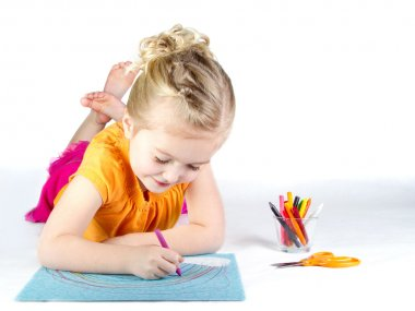 Little girl coloring a rainbow