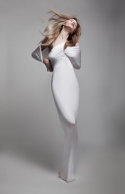 Graceful mystical young woman in white clothes posing in studio