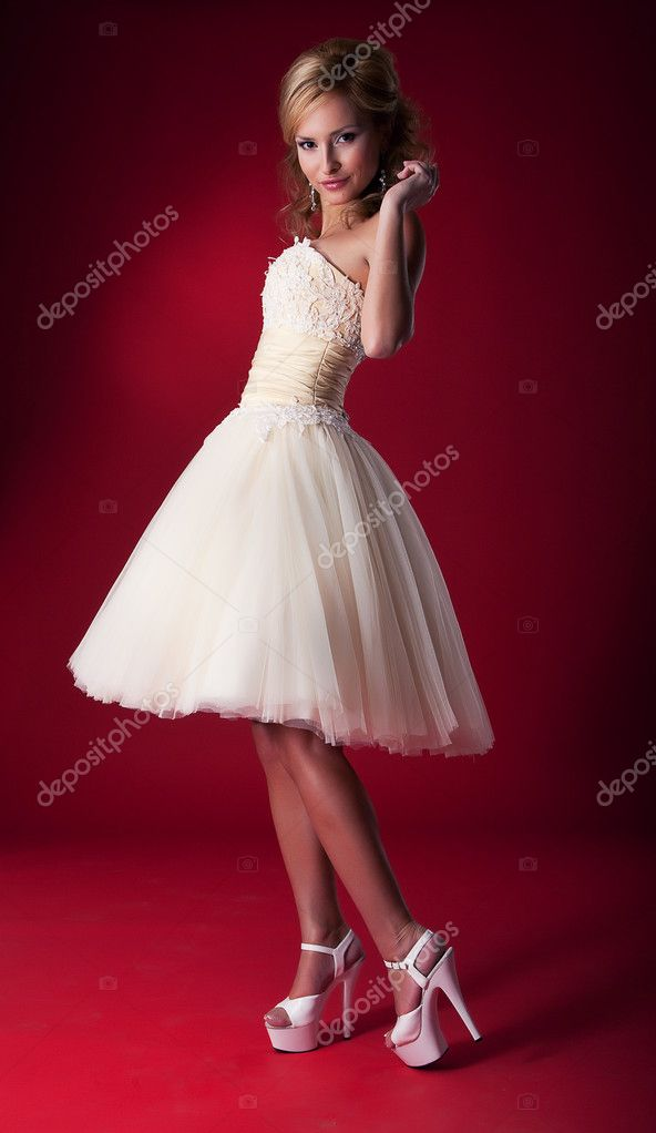 Bride in white nuptial short dress on red background standing on podium