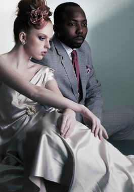 Two fashion models sitting - black man and redhair woman