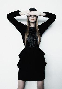 Fashion model blond girl in contemporary black dress posing