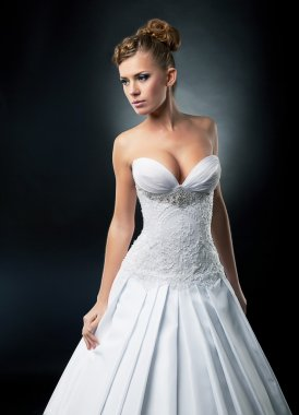 Alluring bride posing in bridal white dress - studio shot