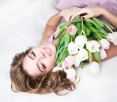 Dreaming lovely young girl with bouquet of flowers