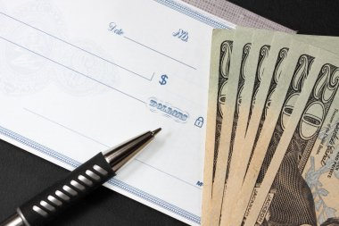 Blank check with twenty dollar bills at its side