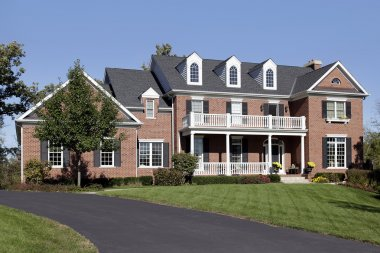 Brick home with front balcony and porch
