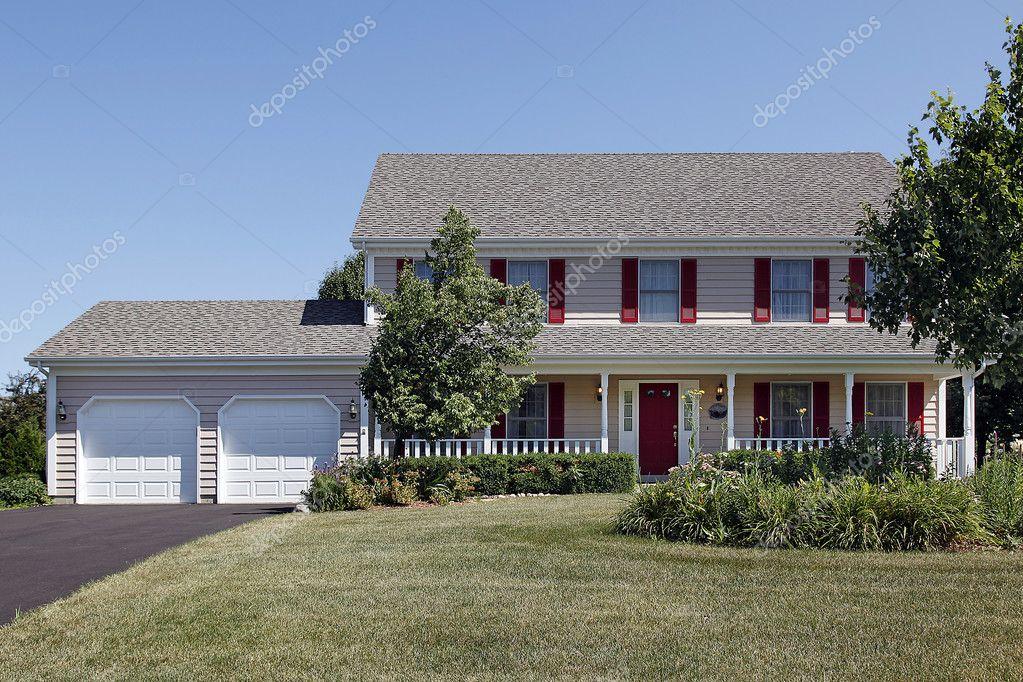 Twee verhaal huis met veranda en rode luiken u stockfoto lmphot