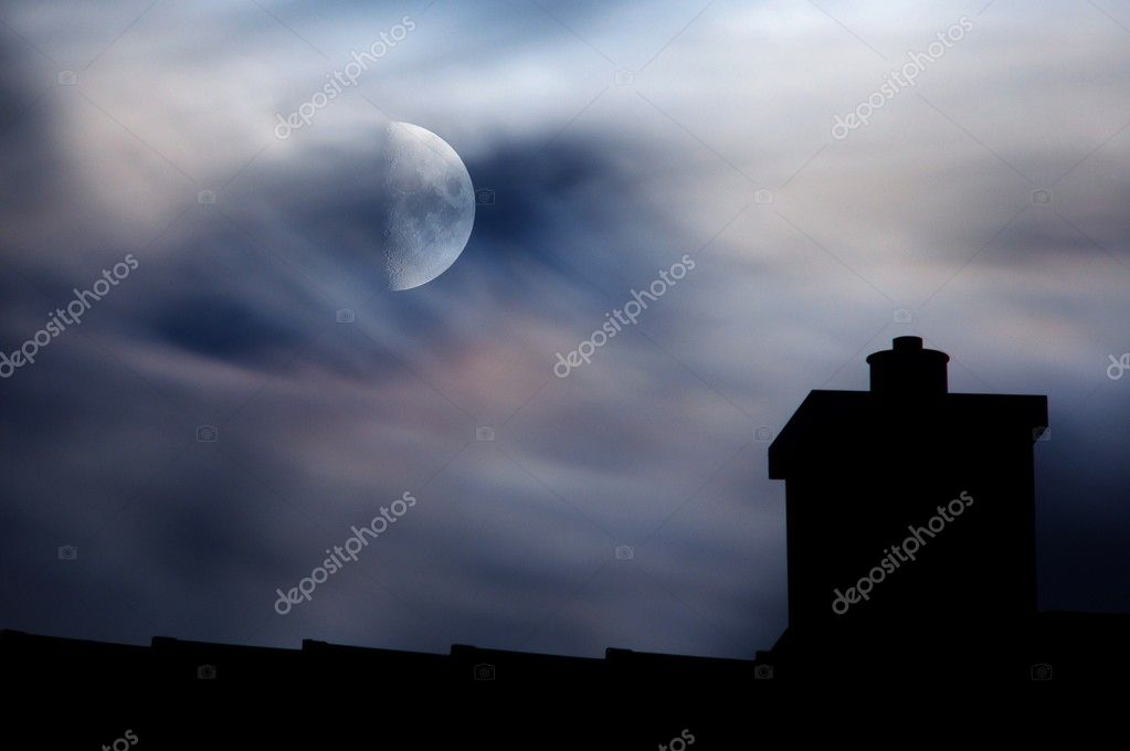 Moonlit clouds above rooftop