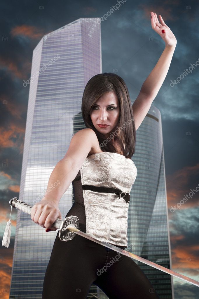 Beautiful girl in a business center with a sword. Angry