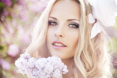 Beautiful woman with flowers of lilac. Skincare
